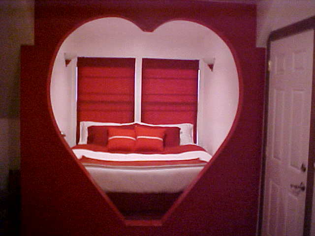 Room with a large bed with entrance to the room being a large shape of the heart.